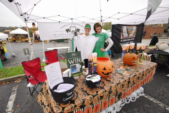 A photo of the Halloween themed table of Dr. Stanislav Family Dentistry at the Clarksville One Frightful Night event. There are lots of pumpkins. Dr. Kristy Dye is wearing a tooth costume. Ronda Burkhart is wearing a tooth fairy costume.