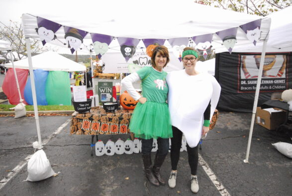 A more close up photo of Dr. Kristy Dye in a tooth costume and Ronda Burkhart in a tooth fairy costume out front of their festive and decorated table.